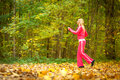 Blonde girl young woman running jogging in autumn fall forest park female runner training outdoor healthy lifestyle outside yellow Royalty Free Stock Photography