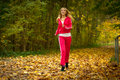 Blonde girl young woman running jogging in autumn fall forest park female runner training outdoor healthy lifestyle outside yellow Stock Photo
