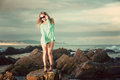 Blonde in green jersey standing on a rock on the beach an attractive young lady wearing is where tide has come she is Stock Images