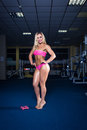 Blonde in the gym. In a pink dress. Royalty Free Stock Photo
