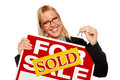 Blonde Holding Keys & Sold For Sale Sign Royalty Free Stock Photography