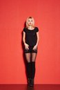 Blonde lady in black posing on red young Royalty Free Stock Image