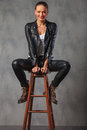 Blonde in leather and boots, posing seated on stool in studio Royalty Free Stock Photo