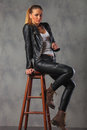 Blonde in leather jacket posing seated on stool in studio Royalty Free Stock Photo