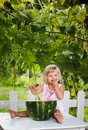 Blonde litle girl eats a slice of watermelon adorable outdoors Stock Image