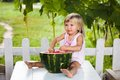 Blonde litle girl eats a slice of watermelon adorable outdoors Stock Photo
