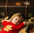 Blonde little boy resting with leaf on stomach lies on wooden floor in autumn leaves. Kid playing in autumn. The biggest Royalty Free Stock Photo