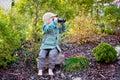 Blonde little toddler child with binoculars, sitting in garden on sunset Royalty Free Stock Photo
