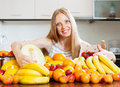 Blonde long haired woman with heap of fruits positive in home kitchen Stock Photography