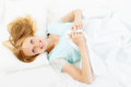 Blonde long haired woman lying on white sheet in bed Stock Image