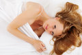 Blonde long haired woman on white sheet in bed at home Royalty Free Stock Photo
