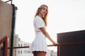Blonde model in white outfit on roof Royalty Free Stock Photo
