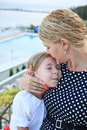 A blonde mother holding her beautiful daughter in her arm and kissing her head Royalty Free Stock Photo