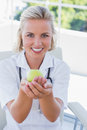 Blonde nurse holding a green apple Royalty Free Stock Photo