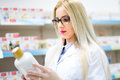 Blonde pharmacist looking at pills and creams in store. Female medical assistant reading on labels Royalty Free Stock Photo