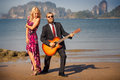 Blonde in red and guitarist on sand at low tide girl high heel shoes bearded playing knee beach Royalty Free Stock Photos