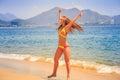 blonde slim girl in bikini expresses joy jumps tip toe on sand Royalty Free Stock Photo