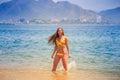 Blonde slim girl in bikini poses in shallow sea water smiles Royalty Free Stock Photo