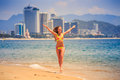 Blonde slim girl in bikini poses smiles on edge of azure sea Royalty Free Stock Photo