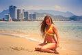 blonde slim girl in bikini sits on heels and bottom on wet sand Royalty Free Stock Photo