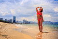 Blonde slim gymnast in bikini stands on sea edge touches hair Royalty Free Stock Photo