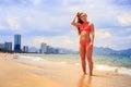 Blonde slim gymnast in bikini stands smiles on edge of sea Royalty Free Stock Photo