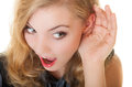 Blonde surprised gossip girl with hand behind ear listening secret Royalty Free Stock Photo