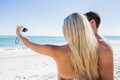 Blonde taking picture of herself with boyfriend at the beach Royalty Free Stock Photos