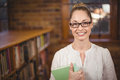 Blonde teacher holding book in the library Royalty Free Stock Photo