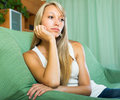 Blonde unhappy woman at home young female in the living room Stock Images