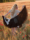 Blonde walking in poppy field Royalty Free Stock Photo