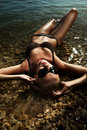 Blonde wearing sunglasses, laying in water Royalty Free Stock Photo