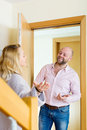 Blonde welcoming boyfriend smiling at entrance of apartment Royalty Free Stock Photos