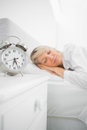 Blonde woman asleep in bed before her alarm clock goes off Stock Photography