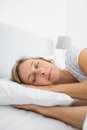 Blonde woman asleep in bed at home bedroom Royalty Free Stock Images
