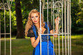 Blonde woman in a bavarian folk costume romantic girl wearing dirndl standing near the cage the garden Royalty Free Stock Photo