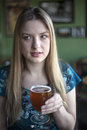 Blonde woman with beautiful blue eyes drinks a goblet of beer portrait drinking Stock Image