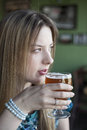 Blonde woman with beautiful blue eyes drinks a goblet of beer portrait drinking Stock Photos