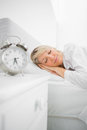Blonde woman in bed asleep before her alarm goes off Stock Images