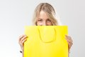 Blonde woman behind yellow shopping bag Royalty Free Stock Photos