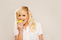 Blonde woman biting an apple Stock Photography