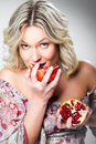 Blonde woman biting pomegranate on gray Royalty Free Stock Photography