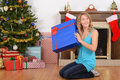 Blonde woman with blue christmas present in front of fireplace Stock Photography