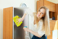 Blonde woman cleaning glass at home Royalty Free Stock Photography