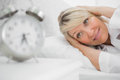 Blonde woman covering her ears from alarm clock noise at home in bed Stock Images