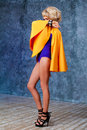 Blonde woman dressed in couture blue bodysuit with yellow cape, extravagant shoes Royalty Free Stock Photo