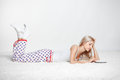 Blonde woman with e book young in pyjamas on white whole floor carpet reading Royalty Free Stock Photo