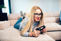 Blonde woman enjoying video games on console while laying on living room sofa