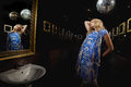 Blonde woman in front of mirror young the restroom with disco ball Royalty Free Stock Photo