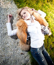 Blonde woman in fur coat lying on grass elegant Royalty Free Stock Image